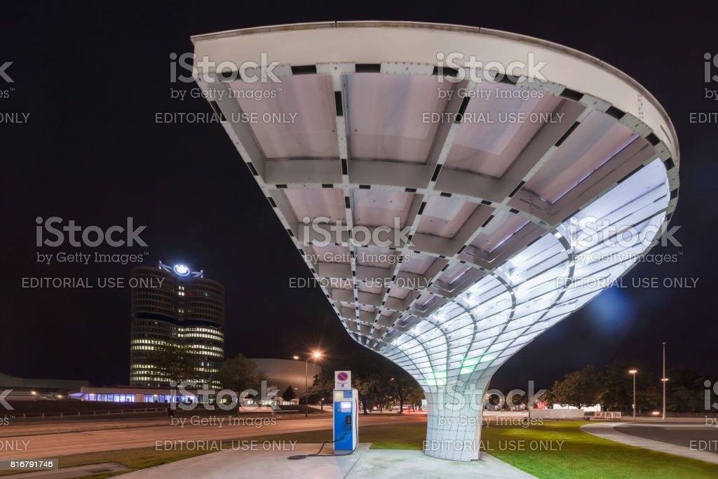 Futuristic architecture of an electric charger for electric cars in front of the illuminated facade of the BMW Welt in Munich at night stock photo
