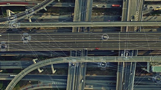 Aerial view from above of traffic on the elevated expressway with futuristic autonomous, driverless cars using artificial intelligence computer network and satellite gps for navigation
