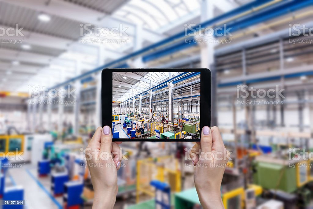 Futuristic factory & female hands holding tablet stock photo