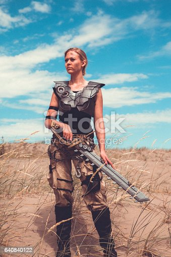 istock Futuristic Female Warrior Standing In The Desert 640840122