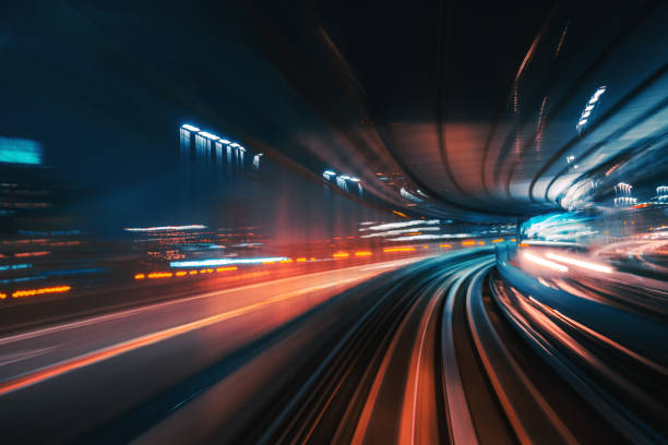 Futuristic High Speed Light Tail with Night City Background High Speed Motion Blur driving through a tunnel at night  Futuristic High Speed Monorail Train Tokyo, Japan the way forward stock pictures, royalty-free photos & images