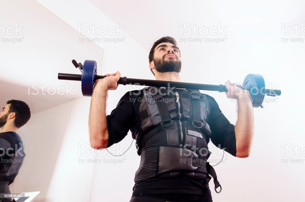 Futuristic image, man exercising with EMS suit on, view from below...