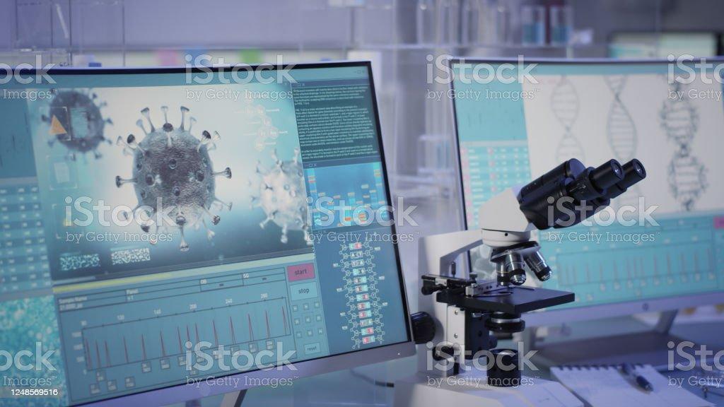 Futuristic laboratory equipment - fighting with coronavirus Modern laboratory interior. Coronavirus research. Word Covid-19 on the screen Biohazardous Substance Stock Photo
