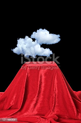 Conceptual cloud computing image of clouds on red velvet pedestal over black background