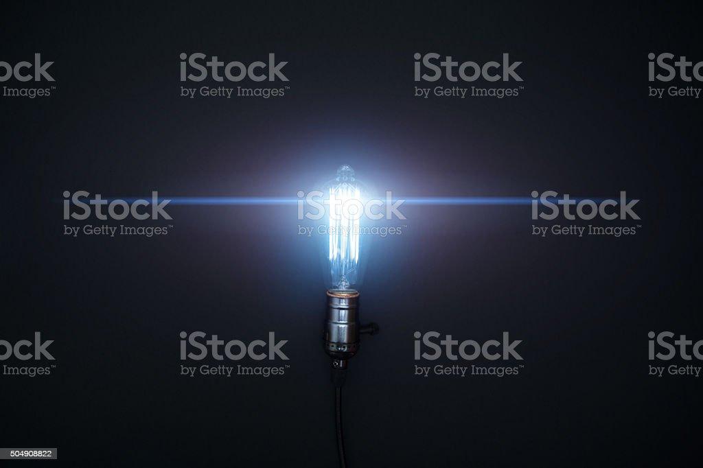 Futuristic light bulb on black background.