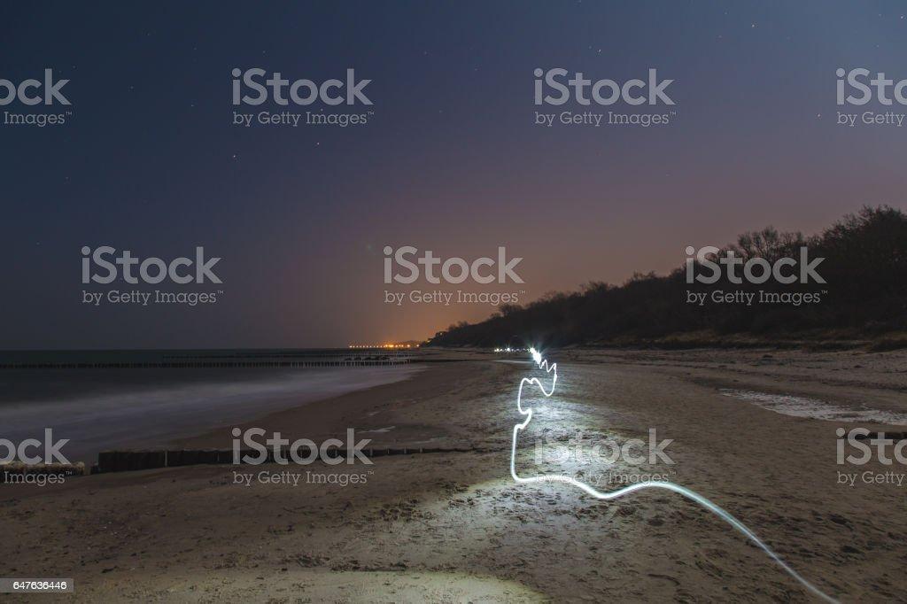 Futuristic light trail on the beach at night stock photo