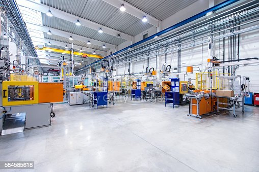 Horizontal image of huge new modern factory with robots and machines producing industrial plastic pieces and equipment. Wide angle view of futuristic machines standing on flooring and having the monopole of all work, taking the place of human work. There is not necessary use human hand. Wide angle, view, no people, space for copy.