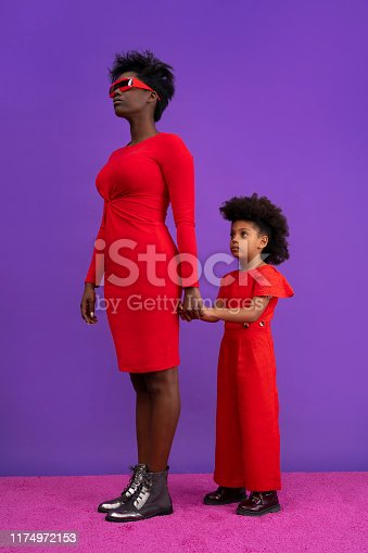 Futuristic mother and daughter in red on purple background holding hand