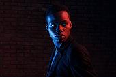 istock Futuristic neon lighting. Young african american man in the studio 1186894112