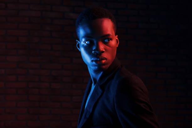 Futuristic neon lighting. Young african american man in the studio stock photo