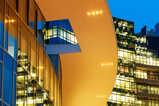 modern bright glass buildings illuminated at dusk in financial district, horizontal orientation, Milan, Italy