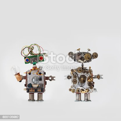 istock Futuristic robots on gray background. Friendly mechanical toys with electrical wire hairstyle, colored blue red eyes, light bulb. Steampunk style handyman made aged gears, cog wheel hand clock parts 655105682