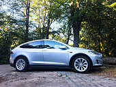 Futuristic Tesla Model X Electric Car Parked in a forest during a beautiful summer day in Breda, Brabant, The Netherlands. The  Model X is a fast SUV that accelerates from zero to 60 miles per hour in 3.2 seconds and is equipped with an autopilot system.