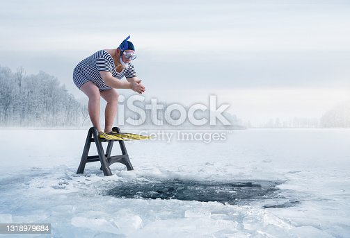 istock Fuunny overweight, retro swimmer about to jump into the ice hole 1318979684
