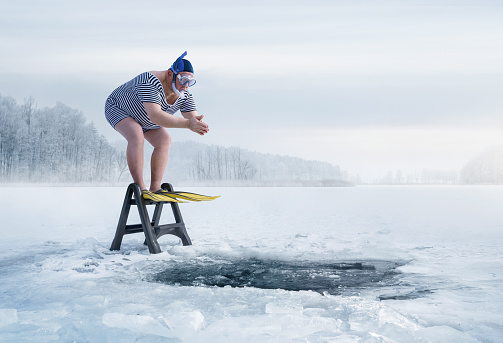 Fuunny overweight, retro swimmer about to jump into the ice hole in the lake, with copy space