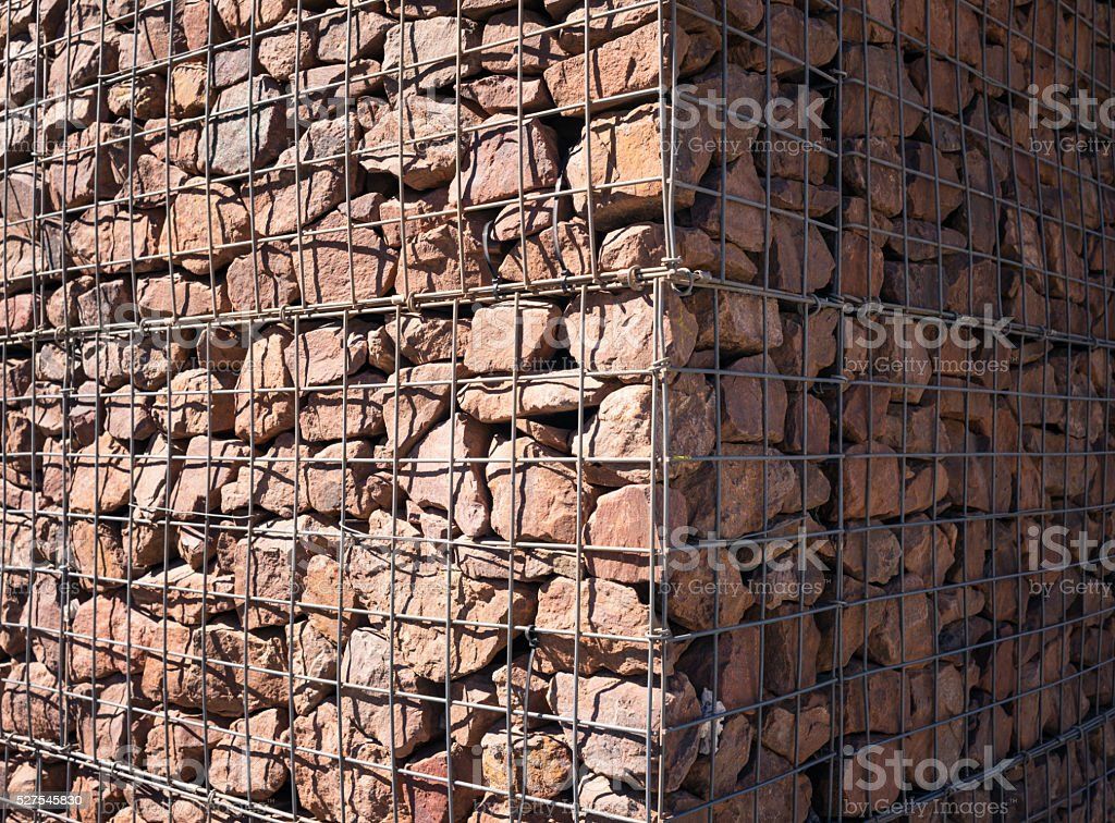 Gabion wall corner: closeup of rock fragments and wire container stock photo