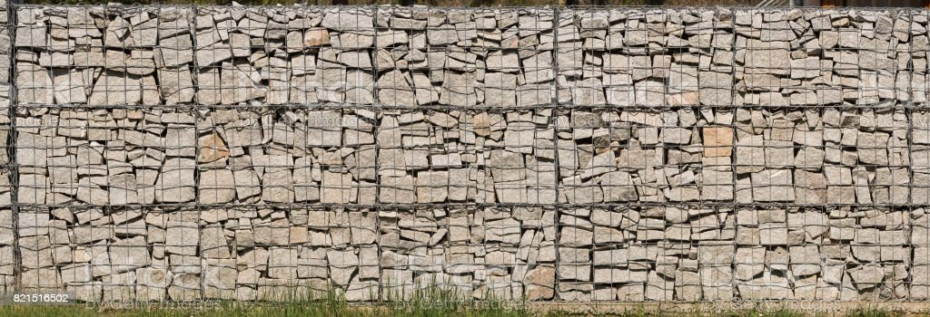 Gabion wall made of grey stones.  Stone wall. stock photo