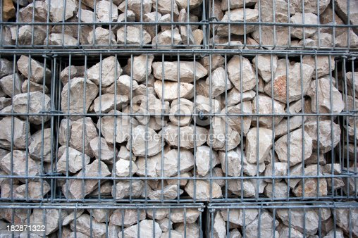 Iron cage filled with rocks to form a wall or a fence in a garden, parking lot, …