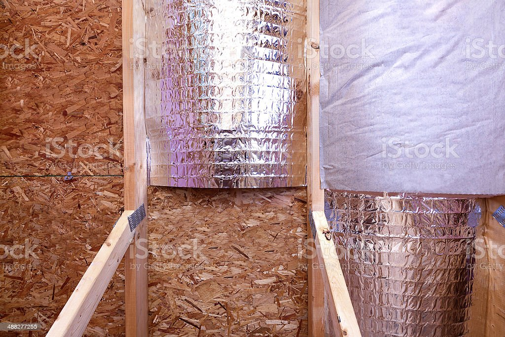 Gable View of Attic insulating with reflective barrier and fiberglass stock photo