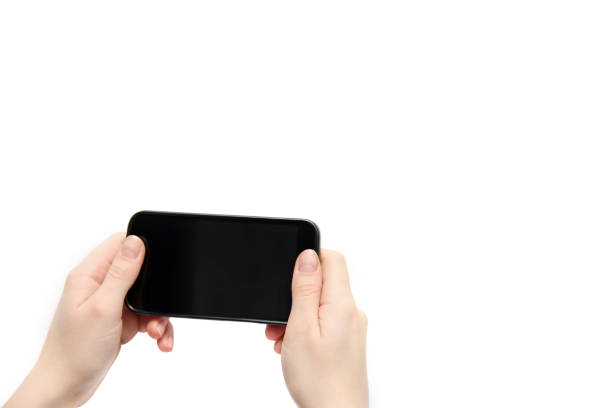 Gadget in the hands. Black phone in hands on a white background stock photo