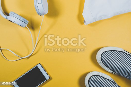istock Gadgets and summer clothes on yellow background 636614524