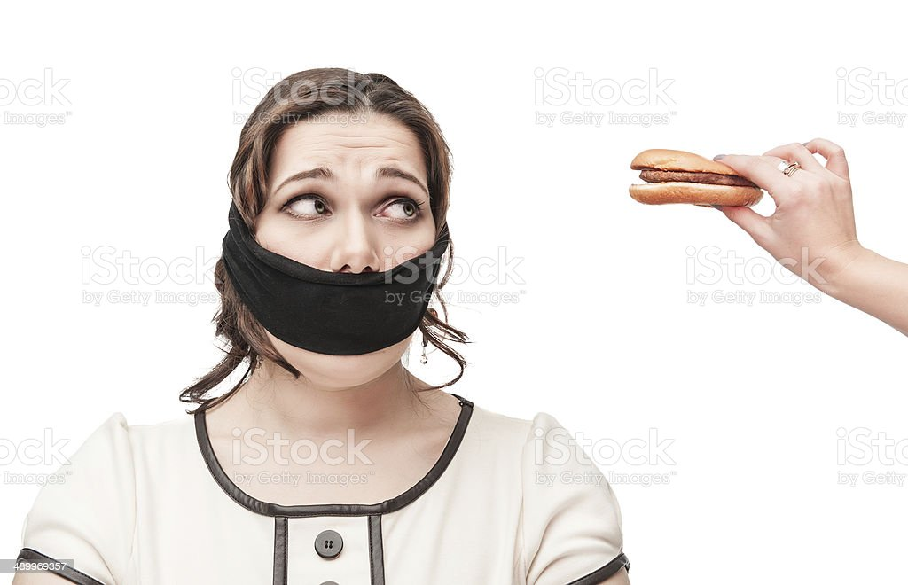 Gagged plus size woman seduced with hamburger royalty-free stock photo