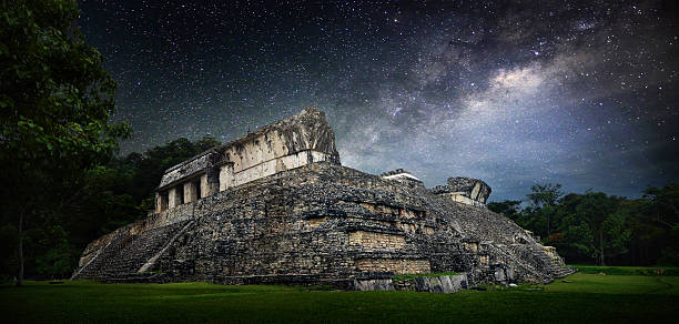 Galactic night starry sky over  ancient Mayan city of Palenque. stock photo