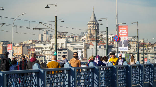 galata bridge in istanbul with galata tower on the background. people walking on bridge. daily life in istanbul. - каракёй стамбул стоковые фото и изображения