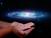A galaxy hovering above the cupped hands of a young girl. Hands illuminated as though being lit by the galaxy. The Galaxy is the Barred Sculptor Galaxy, also known as NGC 253.