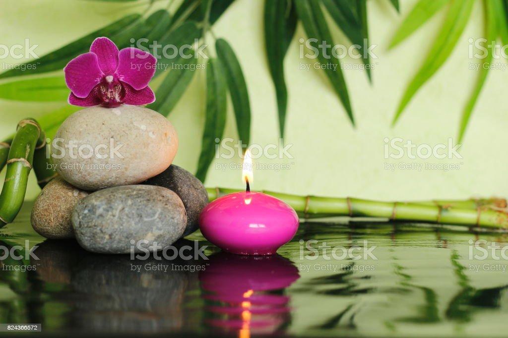 galets disposés en mode de vie zen sur la gauche avec une orchidée au sommet et une bougie rose allumées stock photo