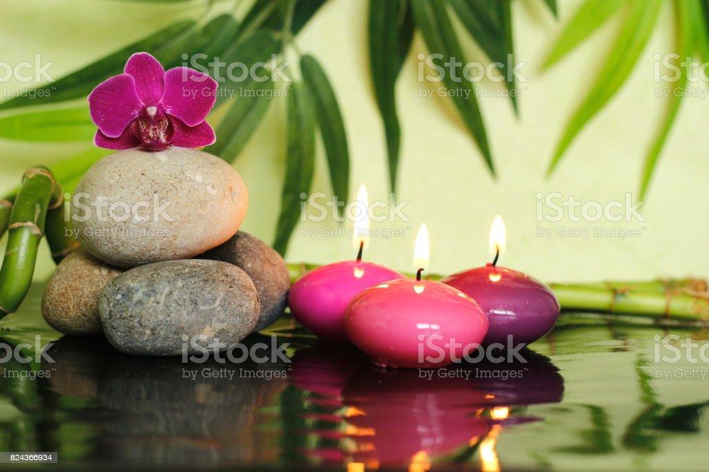 galets disposés en mode de vie zen sur la gauche avec une orchidée au sommet et trois bougies roses allumées stock photo