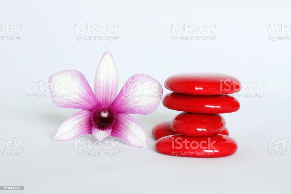 galets rouge disposés en mode de vie zen avec une orchidée sur le coté gauche sur fond blanc stock photo