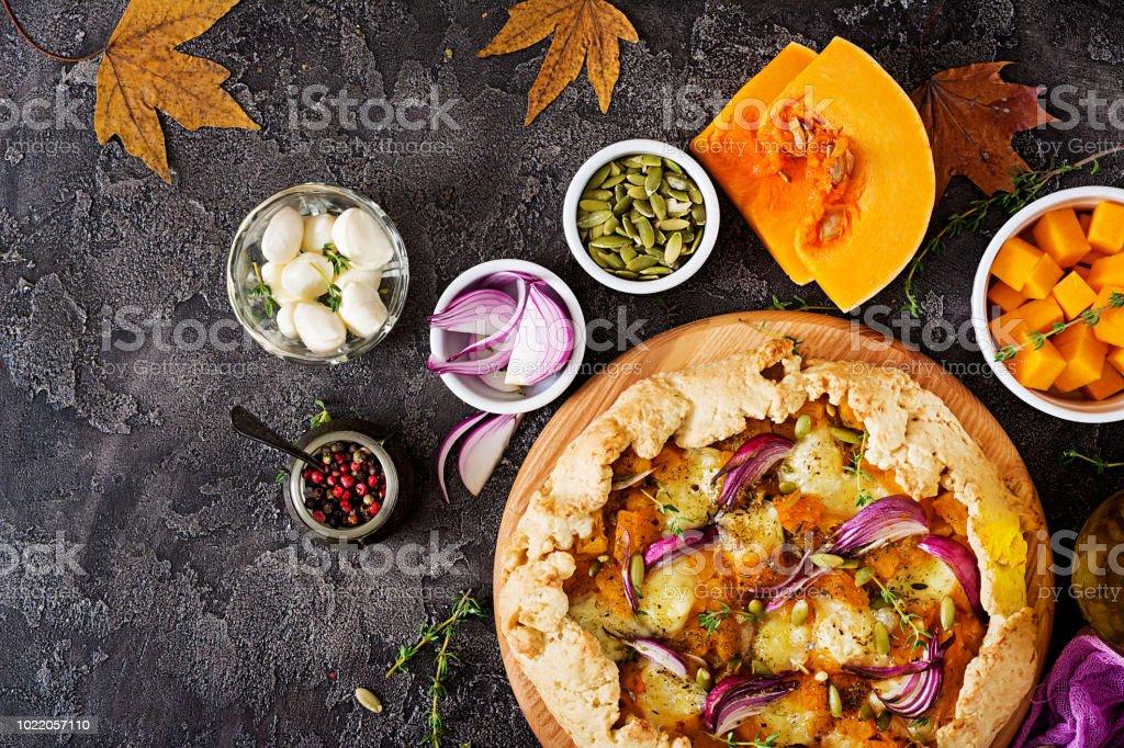 Galette Kuchen mit Kürbis und Mozzarella-Käse auf dunklem Hintergrund. Thanksgiving Day Essen. Ansicht von oben. – Foto