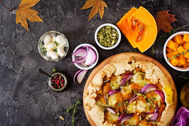 galette kuchen mit kürbis und mozzarella-käse auf dunklem hintergrund. thanksgiving day essen. ansicht von oben. - sommertorten stock-fotos und bilder