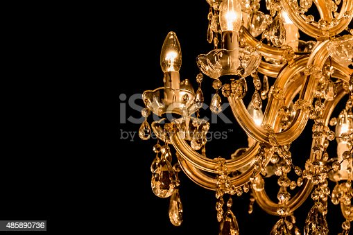 Luxury candelabra hanging on ceiling with lots of little gems. Black Background and copyspace on the left side