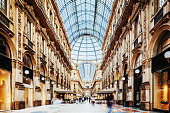 Shot of the famous Galleria Vittorio Emanuele II in Milano, Italy, showing the spectacular view of an almost golden gate to luxury. Long exposure for motion blurred people rushing through.