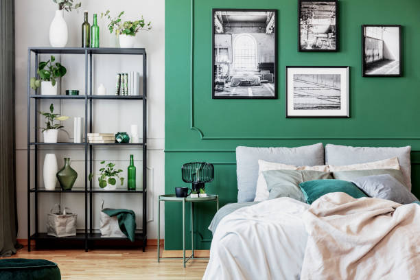 Gallery of black and white poster on green wall behind king size bed with pillows and blanket – zdjęcie