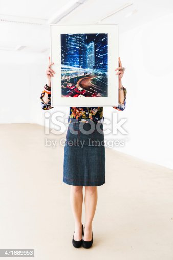 Female gallery owner holding a picture frame with a photography in front of her head. Vertical shot.