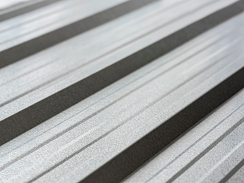 Reflective, abstract, corrugated, galvanized, zinc metal, roofing sheet as a modern architectural feature background showing the character of the ridge profiles.
