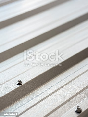 Reflective, abstract, corrugated, galvanized, zinc metal, roofing sheet as a modern architectural feature background showing the character of the ridge profiles. Focus on one of the roof fastener bolts on one of the main profile ridges.