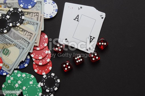 a moment from casino . playing cards and dice and poker chips on the black background.