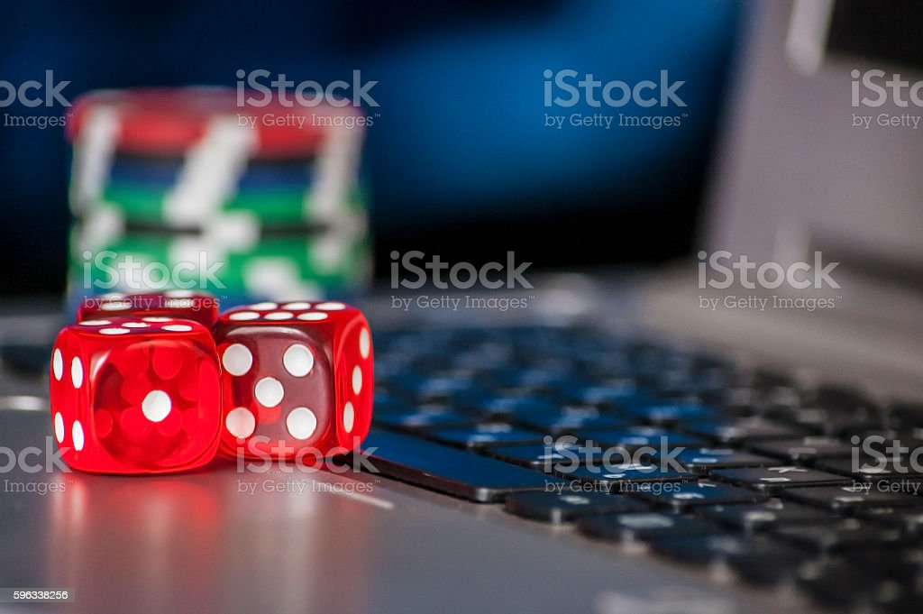 Gambling chips and red dice on laptop keyboard background royalty-free stock photo