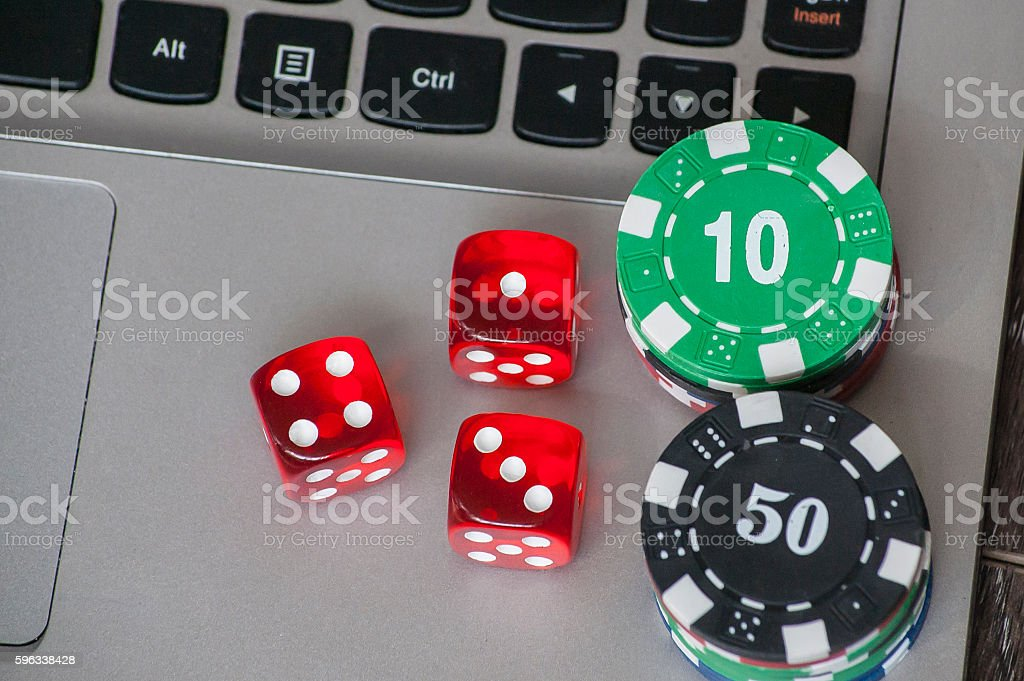 Gambling chips and red dice on laptop keyboard background Lizenzfreies stock-foto