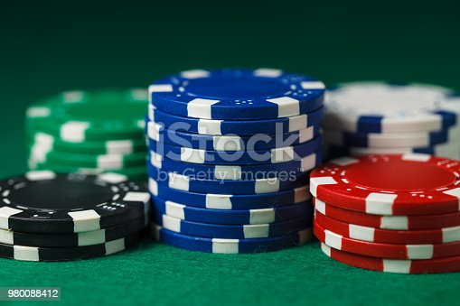 Different colored gambling chips on a green surface.