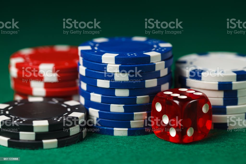 Different colored gambling chips with red dice on a green surface.