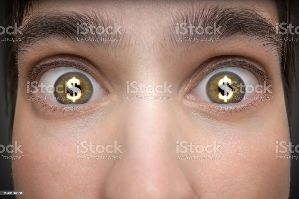 Gambling concept. Young man has dollar signs in his eyes. stock photo