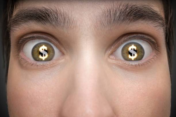 Gambling concept. Young man has dollar signs in his eyes. Gambling concept. Young man has dollar signs in his eyes. greed stock pictures, royalty-free photos & images