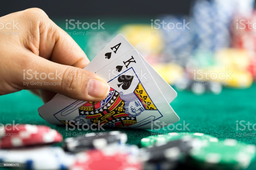 Gambling Hand Holding Poker Cards and Money Coins Chips - foto stock