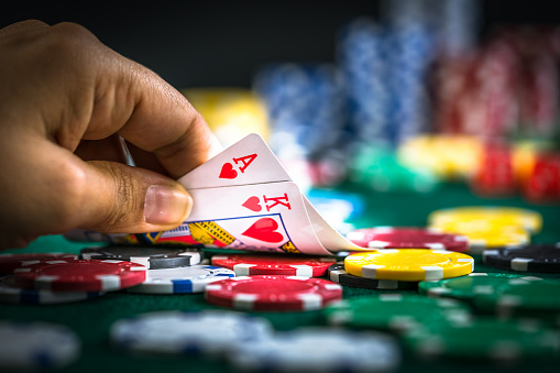 Gambling Hand Holding Poker Cards and Money Coins Chips
