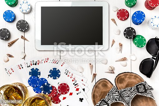 istock Gambling. Poker chips, cards and the dice nearby tablet on wooden table. Top view. Copyspace. Poker 1094965162